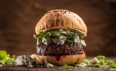 Beef burger with arugula, blue cheese and cranberry sauce.