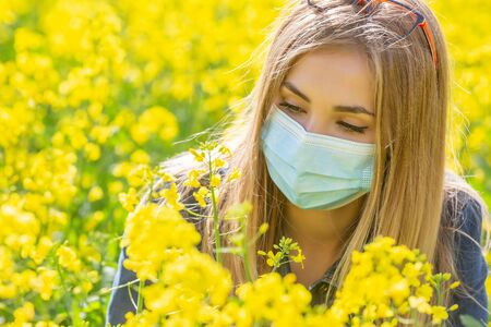 Allergic blonde girl in a protective mask looks at the yellow flower sitting on a meadow.