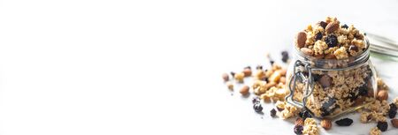 Jar of muesli with nuts, almonds grapes and dried fruits - panoramic banner.
