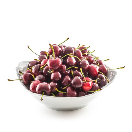 Sweet ripe cherries in bowl isolated on white background.