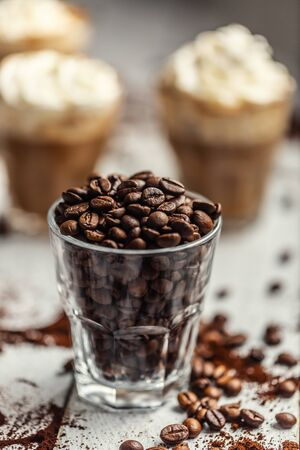 Coffee beans in a glass cup and in the background a cup with coffee and whipped cream.