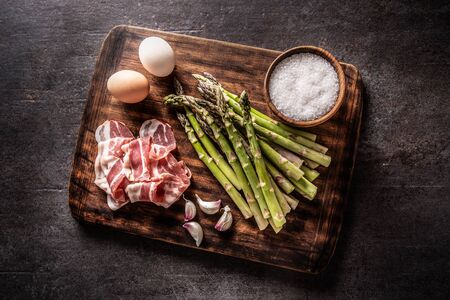 Asparagus eggs bacon and garlic on butcher board. - top of view.