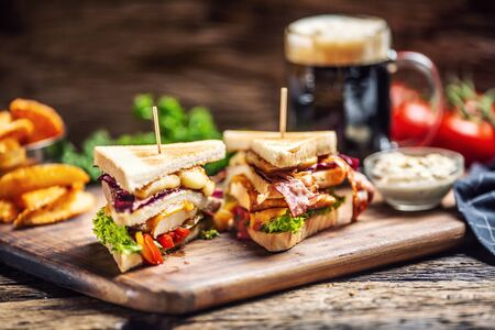 Chicken and cheese sandwich with bacon, red cabbage, peppers and salad with a dark beer in the background.
