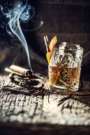 Whisky with no ice in a cup with burning cigar and an old wooden barrel in the background.