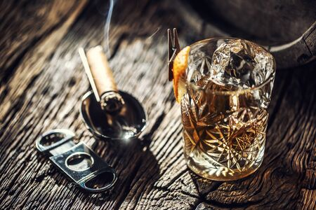 Ornamental glass full of whiskey and ice on a vintage wood next to a cigar cutter and a burning cigar. Standard-Bild