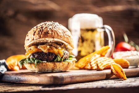Beef burger with caramelized onion, arugula and melted cheese with potato wedges and draft beer in the background.