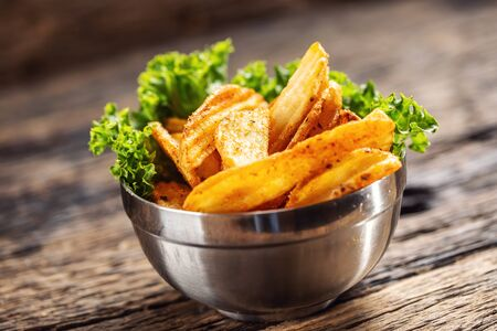 Crispy spiced potato wedges in a metal bowl with salad leaf on dark wood.