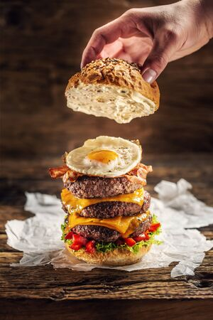 Hand putting the top of bun on a triple cheeseburger with beef patty, egg and peppers in a rustic wooden environment.