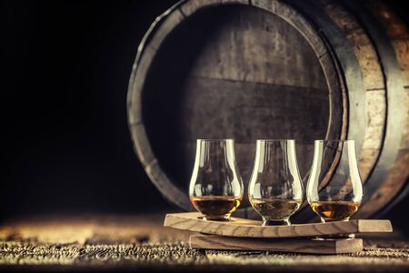 Glencairn whiskey tasting cups on a wooden serving, with a whisky barrel in the dark background.