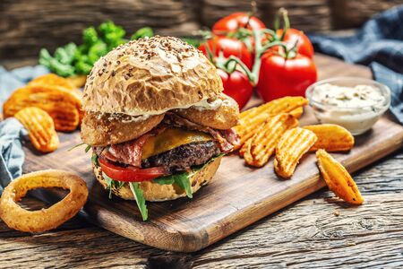 Beef budrger with double cheese, potato wedges, onion ring, tomato, mayonnaise on a dark chopping board.
