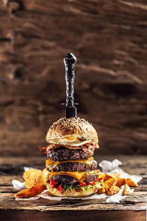 Knife stabbed in a triple cheeseburger with beef patty, melted cheese, egg and peppers in a rustic wooden environment.