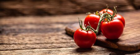 Bunch of fresh tomatoes on a rustic wooden surface.