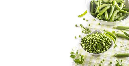 Green raw peas and pods in pocelain bow isolated on white background. Standard-Bild