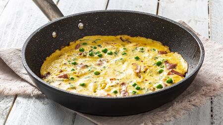 Omelette with prosciutto peas and herbs in ceramic pan on table.