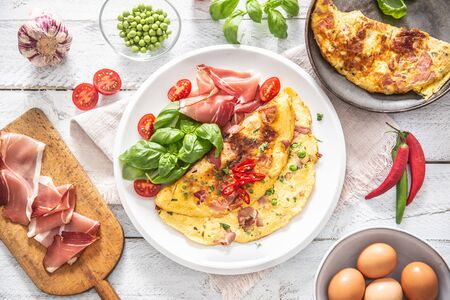 Omelette with prosciutto peas basil tomatoes and herbs on white plate - Top of view.