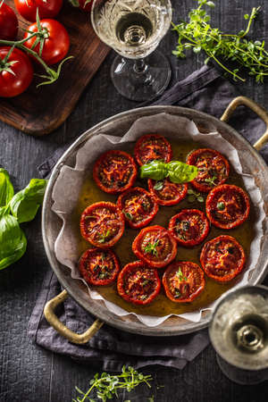 Roasted tomatoes with olive oil thyme oregano basil and white vine - Top of view.