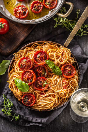 Italian pasta spaghetti with roasted tomatoes basil oregano thyme and white vine - Top of view.