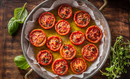 Roasted tomatoes with olive oil thyme oregano and basil in pan - Top of view.