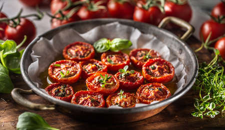 Roasted tomatoes with olive oil thyme oregano and basil in pan.