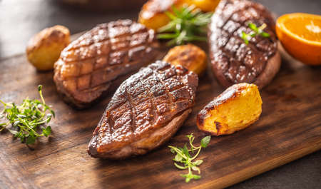 Detail of tasty roasted duck and potatoes on a wooden cutting board.