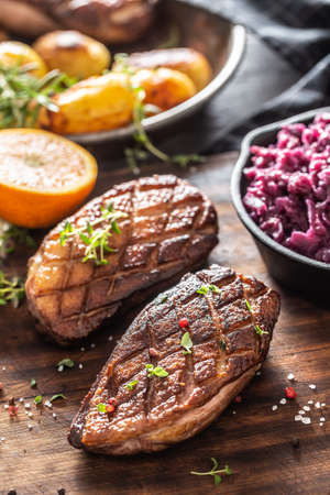 Juicy cooked duck with red cabbage, orange and potatoes on a wooden board.