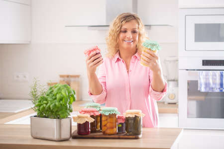 Woman looking at fresh home-made preserves in her hands with more pickles in jars in front of her. Banco de Imagens