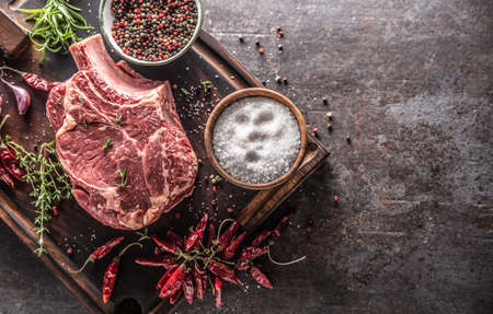 Raw beef steak on wooden cutting board with salt spices chili peppers thyme and rosemary - Top of view.