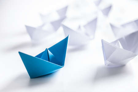 Blue and white paper boats. Concept of leadership boats for teamwork group or success.
