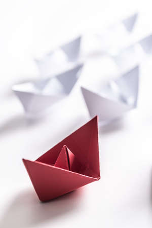 Red and white paper boats. Concept of leadership boats for teamwork group or success.