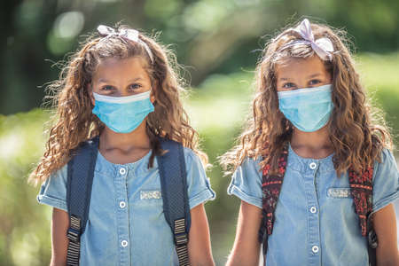The twin sisters with face masks go back to school during the Covid-19 quarantine.