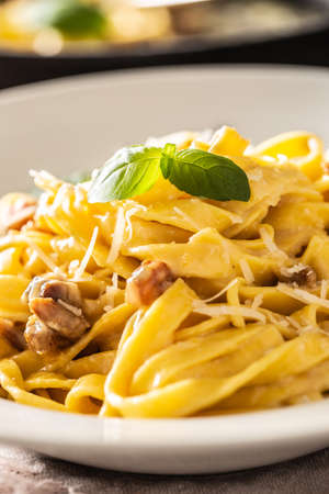 Italian food pasta tagliatelle carbonara with pancetta parmesan egg yolk and basil leaves.