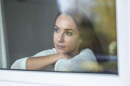 Depressed woman looks out from behind the window with a sad facial expression.
