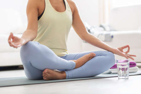 Meditating woman holds a lotus position at home.