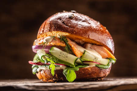 Salmon burger stuffed with vegetable salad avocado and dill.