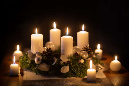 Advent wreath with burning candles christmas balls and decorations.