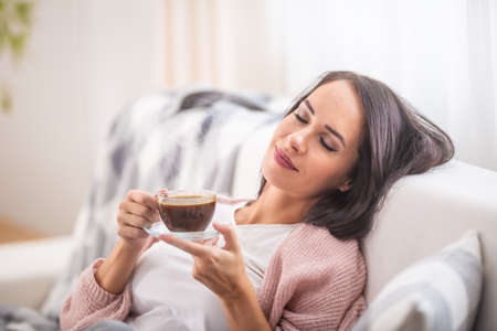 Coffee time relaxing woman on a couch inside the house.
