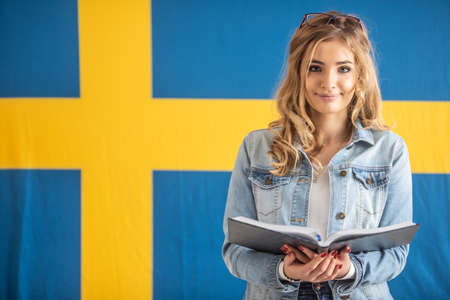 Teenage student with open book stands with Swedish flag behind her. Stockfoto
