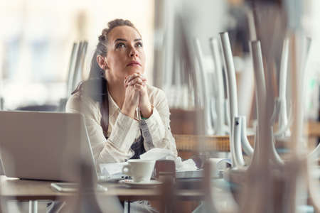 Female business owner prays in a closed restaurant for better times and the end of pandemic.