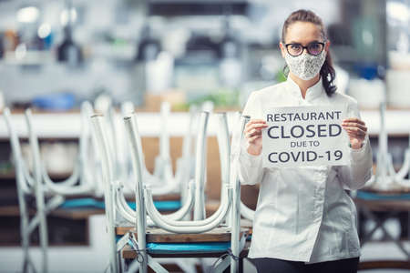Female chef wearing face mask holds a sign saing restaurant closed due to Covid-19.