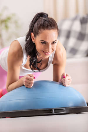 Woman focuses on holding the plank position on elbows during a home workout on a balance ball.