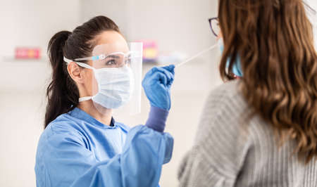 Female medical staff worker wearing protective equipment takes sample from nose of a patient to antigen test for coronavirus. Stock Photo