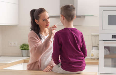 Home testing for Covid-19 as mum puts swab into the nose of her son sitting on a kitchen desk.