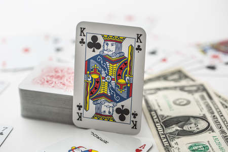 King card with pile of other cards next to a dollar bank notes.