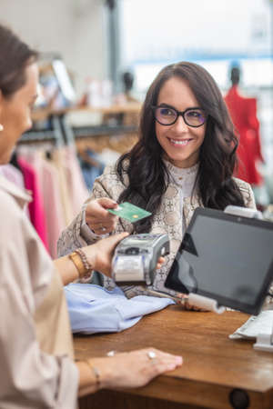 Contactless payment done by a female customer as shop assistant holds the terminal in her hand in a fashion shop. Stock Photo