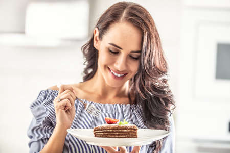 Layered brown adn white cake with strawberry and mint leaf on top held by a woman with a fork.