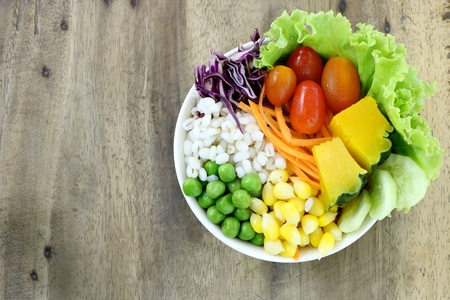 healthy and diet food , fresh vegetable salad (lettuce, tomato, pumpkin, carrot, corn, millet, cucumber, purple  cabbage and peanuts) in white bowl on wood table background have copy space