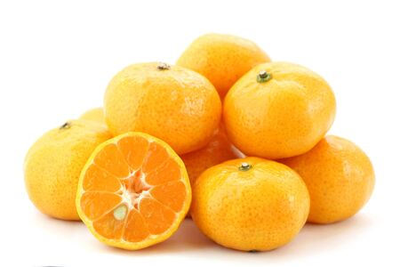 Pile of many orange fruits on white background, side view, have some have some piece sliced can see seed inside.