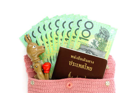Top view of Australian cash money with Thai passport and kangaroo pen out from pink bag on white background. Concept travel by yourself or tour or go to learn at Australia