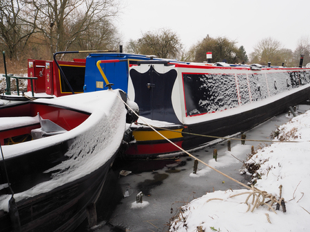 Colorful canal boats moored in icy water during winter snow, Kennet and Avon Canal, Aldermaston, Berkshire, UK