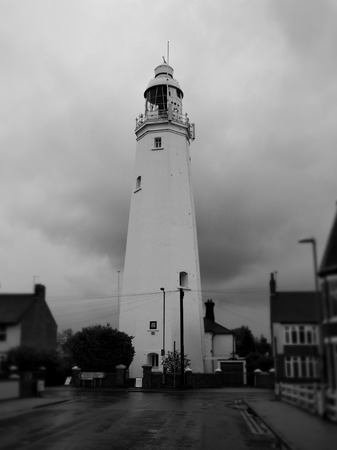 Withernsea Lighthouse, an inland lighthouse that stands in the middle of the town, taken on a stormy day with dark clouds and set against the background of blurred houses, shot in monochrome, UK